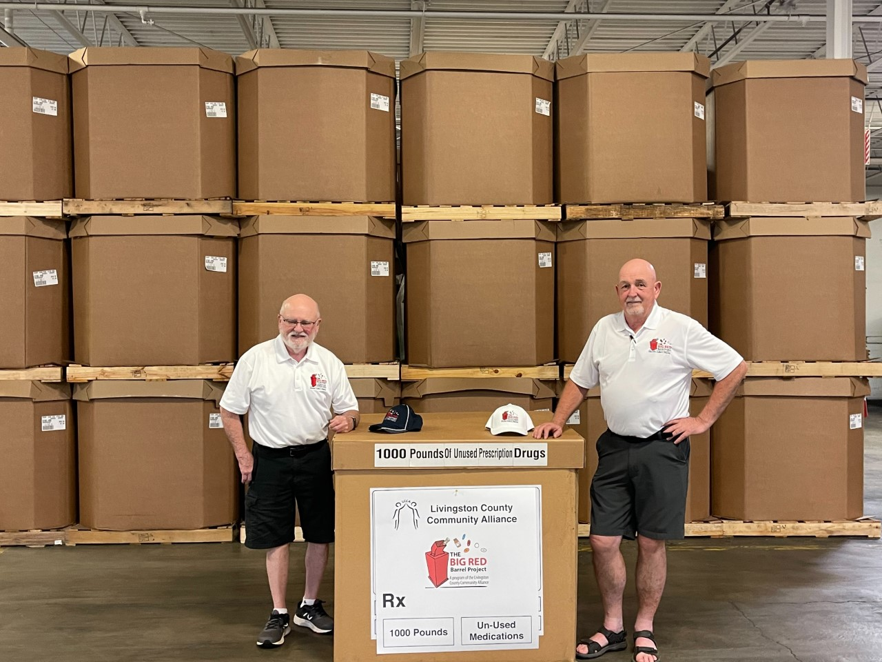 Joe Carney and Terry Murray standing with a box representing 10,000ls of pills collected